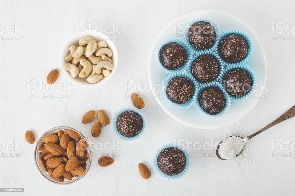 チョコレートの健康、エネルギーはナッツ、日付、ココア パウダー、ココナッツと白いテーブルにフレークをかみます。 ストックフォト