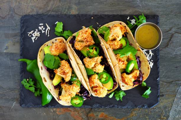 Healthy coconut cauliflower tacos, above on dark slate stock photo