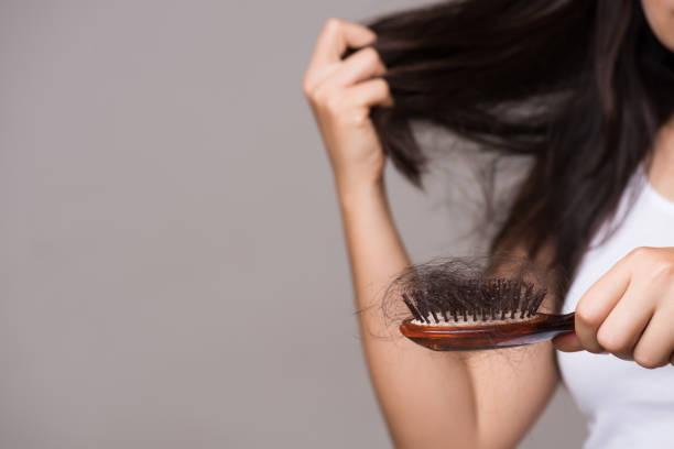 Gesundes Konzept. Frau zeigt ihren Pinsel mit langen Verlusthaaren und schaut auf ihr Haar. – Foto