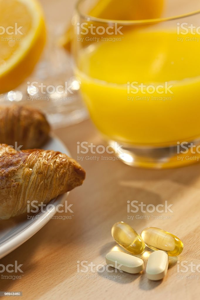 Healthy Continental Breakfast Croissant Orange Juice, Vitamin and Oil Tablets royalty-free stock photo