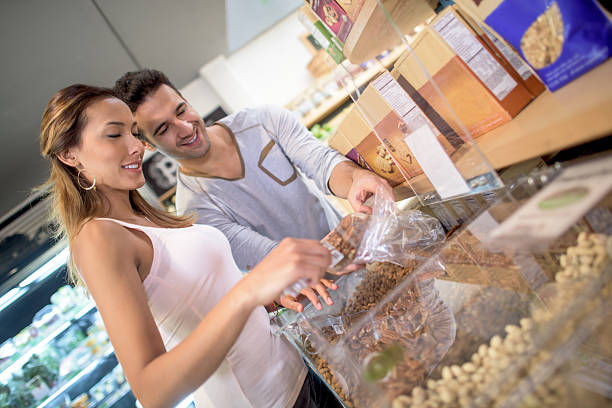 healthy couple buying cereals at the market - glutenfrei einkaufen stock-fotos und bilder