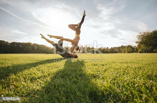 istock Healthy couple doing acro yoga on grass 626683046