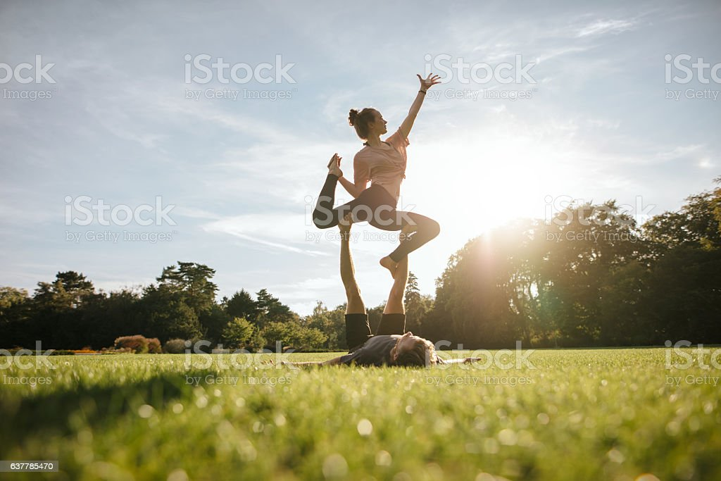Healthy couple doing acro yoga on grass – Foto