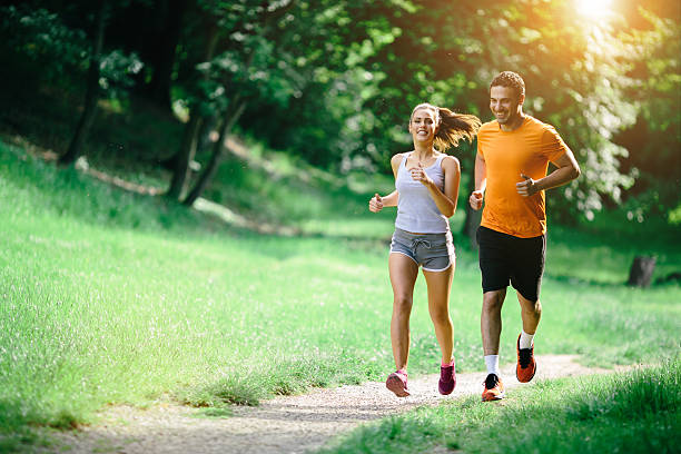healthy couple jogging in nature - jogging stock pictures, royalty-free photos & images