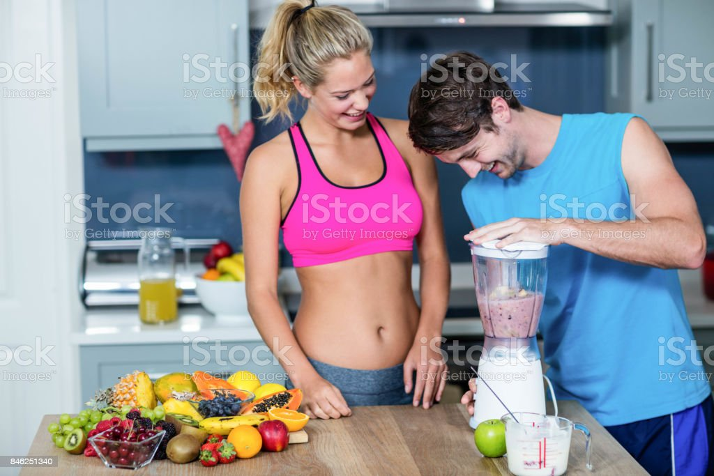 Healthy couple preparing a smoothie stock photo