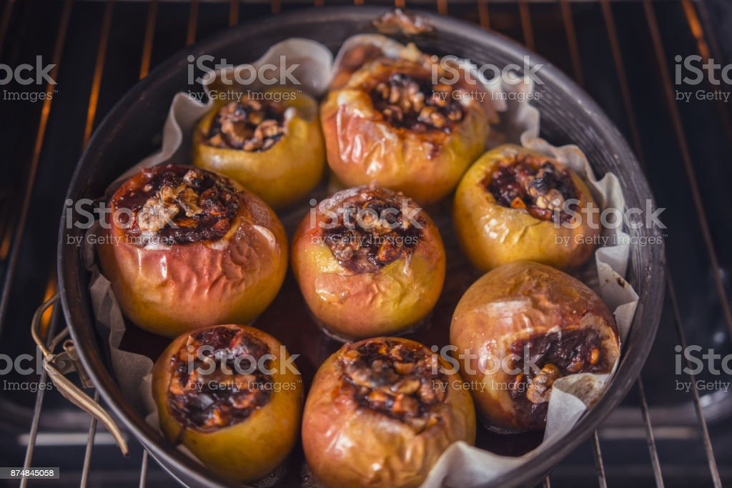 Healthy dessert, apple with nuts and baked jam in the oven stock photo
