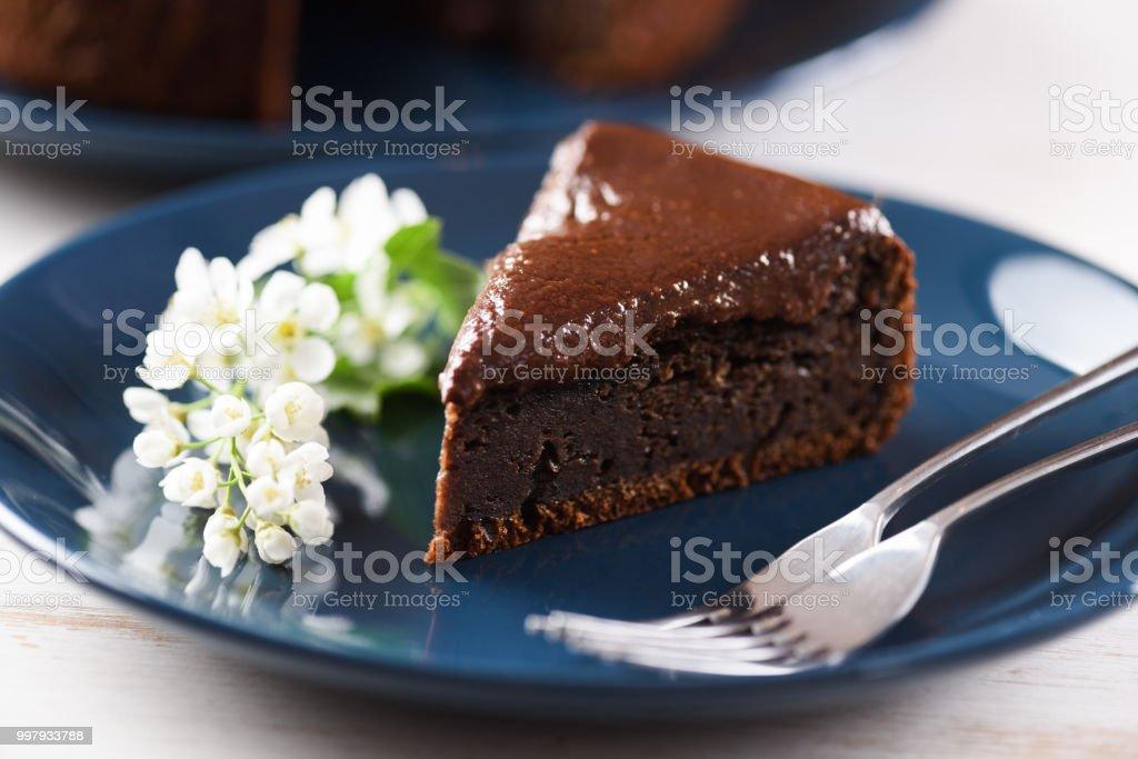 Postre saludable. Pastel de cereza de pájaro con glaseado de chocolate decorado con flores de la cereza de pájaro en placa azul - foto de stock