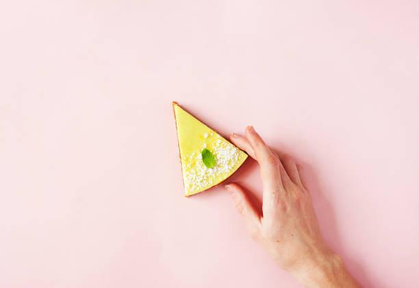 healthy dessert - raw vegan lemon and coconut cake on pink background with woman hand - modern summer food minimal concept, copy space - кусок торта стоковые фото и изображения