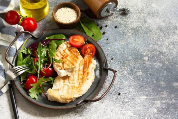 건강 한 다이어트 여름 점심. 회색 돌 조리대에 야채 샐러드와 구운 치킨 필레. 공간을 복사합니다. 스톡 사진