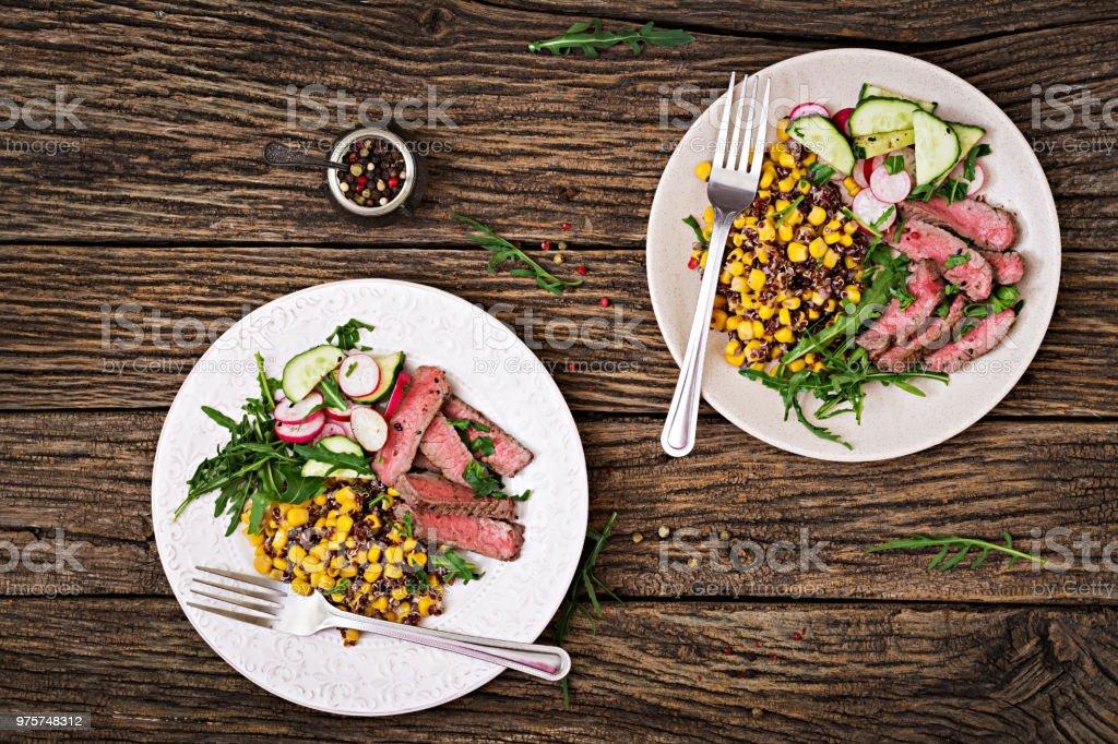 Gesundes Essen. Schüssel Mittagessen gegrilltes Rindersteak und Quinoa, Mais, Gurken, Radieschen und Rucola auf hölzernen Hintergrund. Fleisch-Salat. Flach zu legen. Ansicht von oben - Lizenzfrei Antioxidationsmittel Stock-Foto