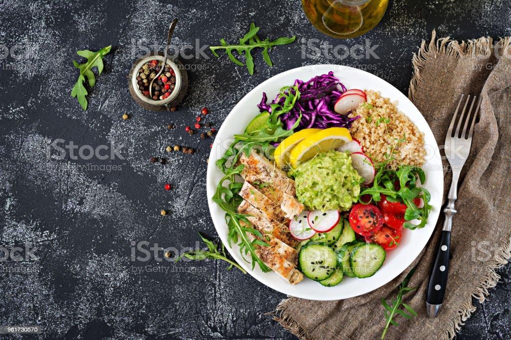 Gesundes Essen. Buddha Schüssel Mittagessen mit gegrilltem Hähnchen und Quinoa, Tomaten, Guacamole, Rotkohl, Gurken und Rucola auf grauem Hintergrund. Flach zu legen. Ansicht von oben – Foto