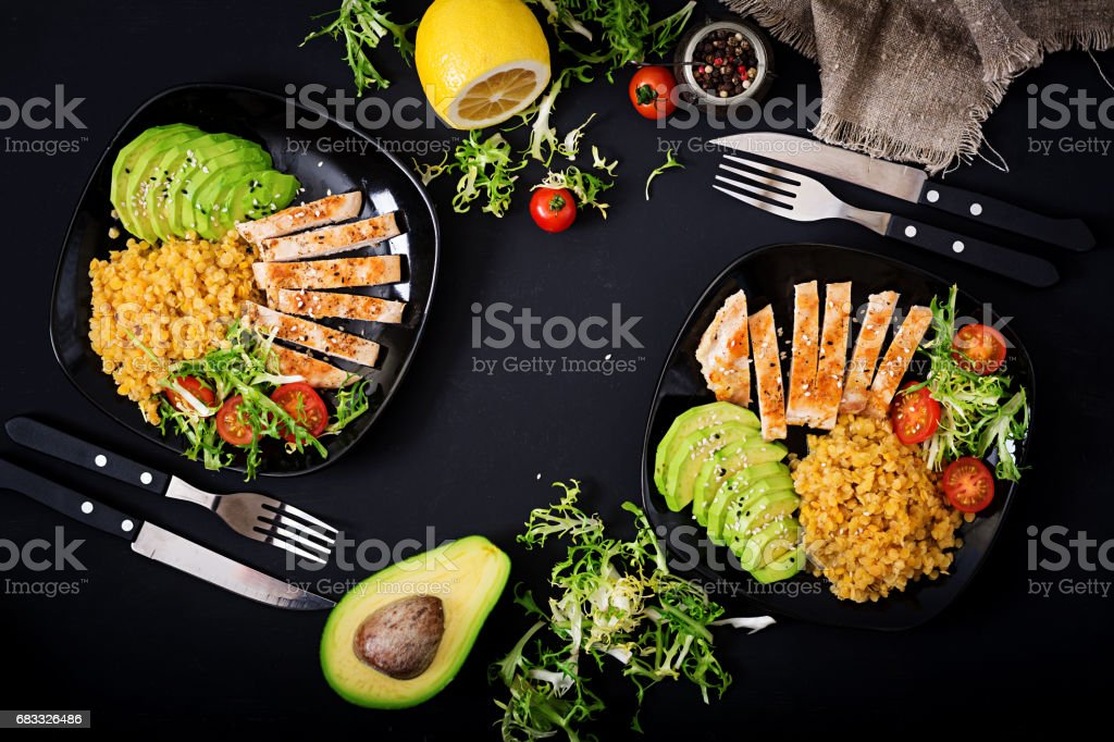 Healthy dish with chicken, tomatoes,  avocado, lettuce and lentil on dark  background. Dinner . Flat lay. Top view royalty-free stock photo