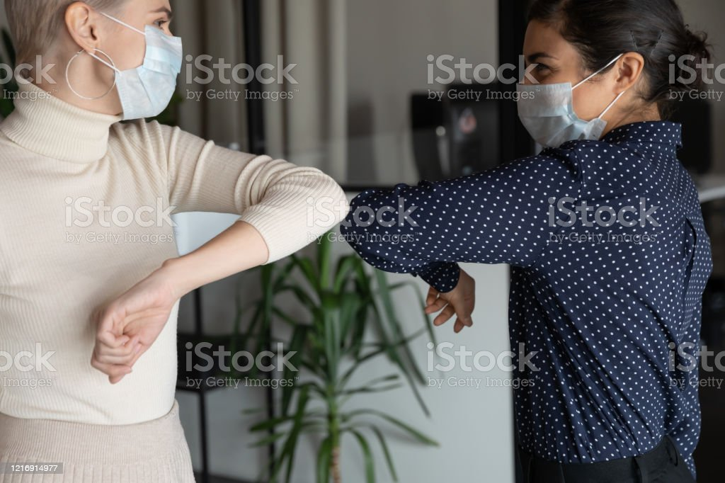 Healthy diverse colleagues in facial masks bumping elbows. Smiling young healthy mixed race female colleagues wearing facial medical masks greeting each other by bumping elbows gesture at workplace keeping social distance, preventing spreading covid19 virus. Adult Stock Photo