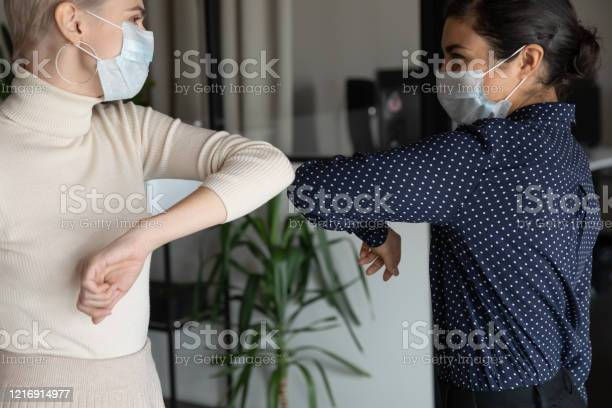 Healthy Diverse Colleagues In Facial Masks Bumping Elbows Stock Photo - Download Image Now