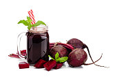 Healthy drink: mason jar filled with fresh organic beet juice shot on white background. Whole and sliced beets are all around the glass. The composition is at the left of an horizontal frame leaving a useful copy space for text and/or logo. Predominant colors are purple and white. High key DSRL studio photo taken with Canon EOS 5D Mk II and Canon EF 100mm f/2.8L Macro IS USM.