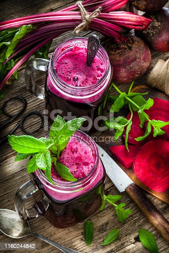 Healthy drink: high angle view of two drinking glasses filled with fresh organic beet juice shot on rustic wooden kitchen table. Whole and sliced beets are all around the glasses. A kitchen knife, spoon and some mint twigs complete the composition. Predominant colors are purple, green and brown. Low key DSRL studio photo taken with Canon EOS 5D Mk II and Canon EF 100mm f/2.8L Macro IS USM.