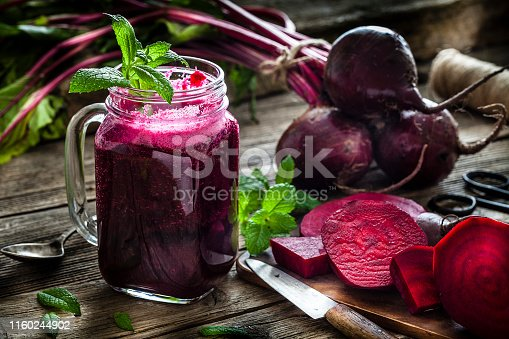 Healthy drink: drinking glass filled with fresh organic beet juice shot on rustic wooden kitchen table. Whole and sliced beets are all around the glass. A kitchen knife, spoon and some mint twigs complete the composition. Predominant colors are purple, green and brown. Low key DSRL studio photo taken with Canon EOS 5D Mk II and Canon EF 100mm f/2.8L Macro IS USM.