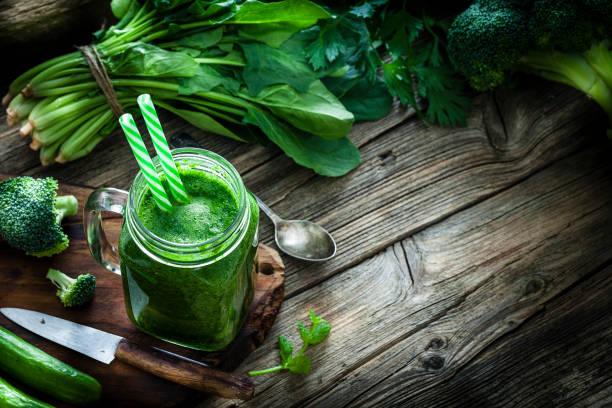 zdrowy napój: sok z zielonych warzyw na rustykalnym drewnianym stole z kopią - detoks zdjęcia i obrazy z banku zdjęć