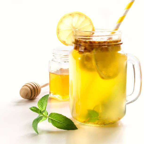 gesundes getränk von sanddorn, zitrone und minze im einmachglas auf weißem hintergrund. - heiße zitrone stock-fotos und bilder