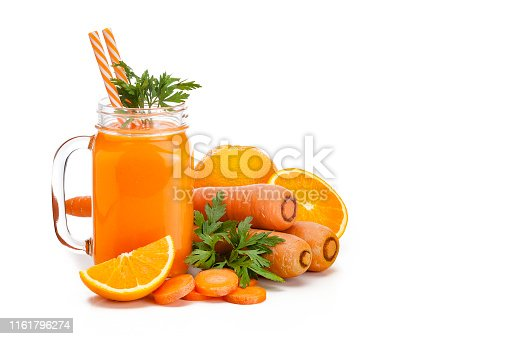 Healthy drink: mason jar filled with fresh organic orange and carrot juice shot on white background. Whole and sliced carrots and oranges are all around the glass. The composition is at the left of an horizontal frame leaving a useful copy space for text and/or logo. Predominant colors are orange and white. High key DSRL studio photo taken with Canon EOS 5D Mk II and Canon EF 100mm f/2.8L Macro IS USM.