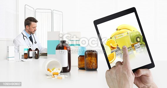 1175869940istockphoto healthy eating and diet concept, hand pointing fruits on digital tablet screen, doctor in medical office desk with pills, bottle tablets and supplements 1093490902