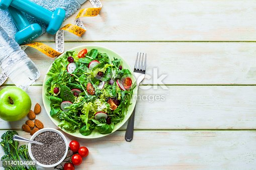 Healthy eating and exercising backgrounds: Top view of a fresh organic salad plate, dumbbells, towel, water bottle, tape measure, almonds and an apple placed at the left of an horizontal frame leaving useful copy space for text and/or logo at the right. A bowl with chia seeds is included in the composition. Predominant color is green. High key DSRL studio photo taken with Canon EOS 5D Mk II and Canon EF 100mm f/2.8L Macro IS USM.