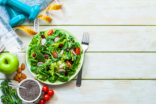 istock Healthy eating and exercising backgrounds: Fresh healthy salad, dumbbells and tape measure with copy space 1140104666