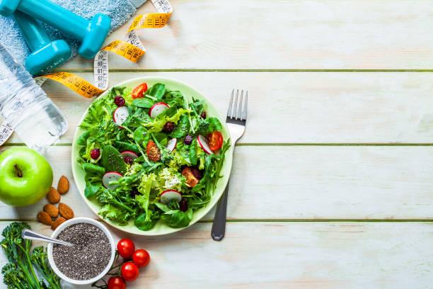 Gesundes Essen und Bewegung im Hintergrund: Frischer gesunder Salat, Hanteln und Tonbandmaß mit Kopierplatz – Foto