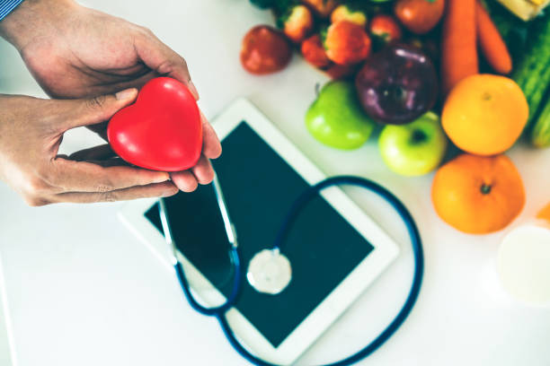 Healthy eating and good nutrition concept. Diet food of fruit and vegetables for cholesterol control with nutritionist hands showing awareness and prevention of heart disease. Healthy eating and good nutrition concept. month stock pictures, royalty-free photos & images