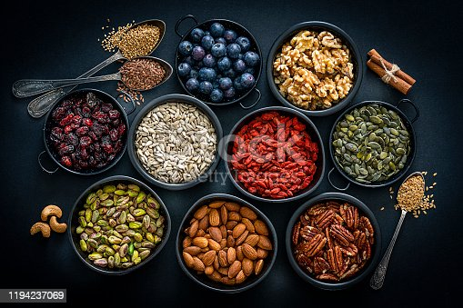 Healthy eating: top view of several small bowls filled with nuts, seeds and fruits sitting on black background. The composition includes blueberries, goji berries, pecan, pumpkin seeds, walnuts, almonds, sunflower seeds, cinnamon sticks and cashew. High resolution 42Mp studio digital capture taken with Sony A7rii and Sony FE 90mm f2.8 macro G OSS lens