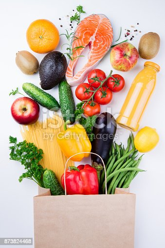 istock Healthy eating background. Healthy food in full paper bag of different products fish, vegetables and fruits on white background 873824468