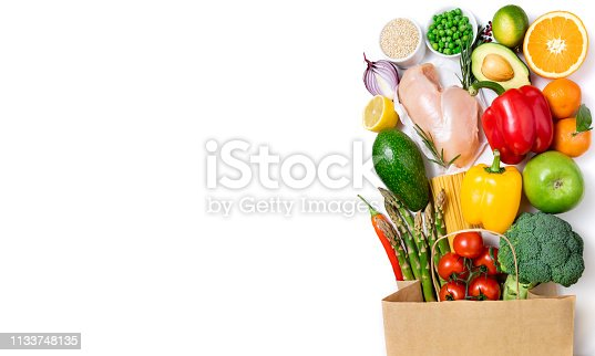 1126188273 istock photo Healthy eating background. Healthy food in paper bag meat, fruits, vegetables and pasta on white background. Shopping food in supermarket, dieting concept. Long format 1133748135
