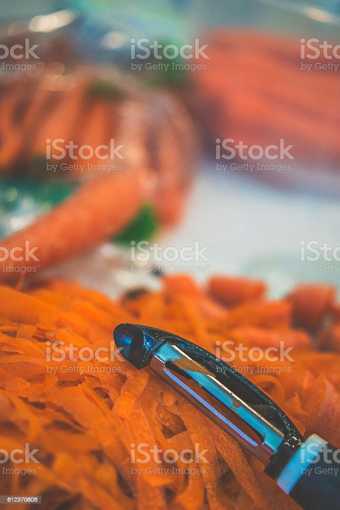 Healthy eating. Carrot peeler with organic carrots on kitchen counter