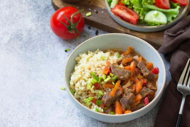건강한 식생활 개념. 불거 소스를 곁들인 채소와 신선한 야채 샐러드를 가벼운 돌 테이블 위에 얹은 소고기. 공간을 복사합니다. 스톡 사진