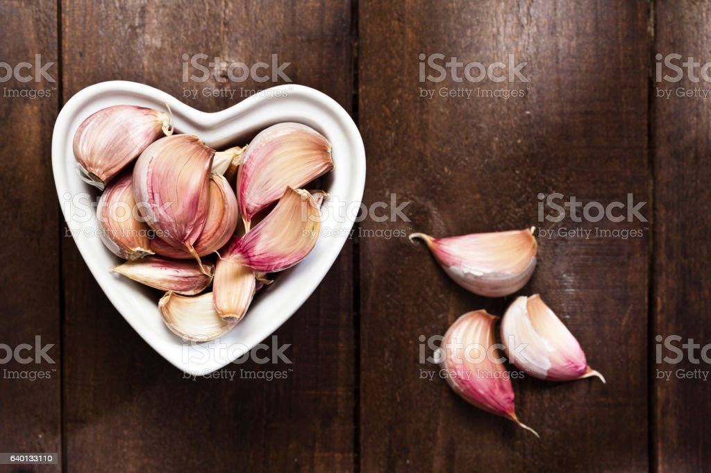 Healthy eating concept: heart shaped bowl filled with garlic cloves stock photo