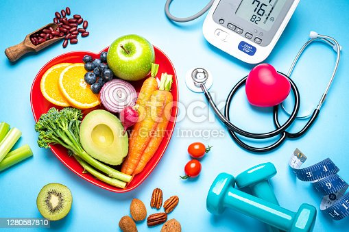 Healthy lifestyle concepts: red heart shape plate with fresh organic fruits and vegetables shot on blue background. A digital blood pressure monitor, doctor stethoscope, dumbbells and tape measure are beside the plate  This type of foods are rich in antioxidants and flavonoids that prevents heart diseases, lower cholesterol and help to keep a well balanced diet. High resolution 42Mp studio digital capture taken with SONY A7rII and Zeiss Batis 40mm F2.0 CF lens