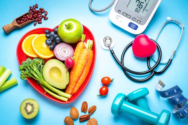 Healthy eating, exercising, weight and blood pressure control Healthy lifestyle concepts: red heart shape plate with fresh organic fruits and vegetables shot on blue background. A digital blood pressure monitor, doctor stethoscope, dumbbells and tape measure are beside the plate  This type of foods are rich in antioxidants and flavonoids that prevents heart diseases, lower cholesterol and help to keep a well balanced diet. High resolution 42Mp studio digital capture taken with SONY A7rII and Zeiss Batis 40mm F2.0 CF lens healthy heart stock pictures, royalty-free photos & images
