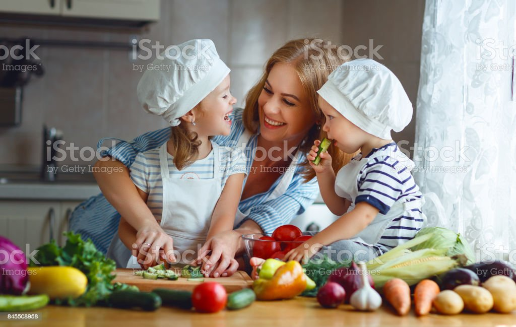 Healthy eating. Happy family mother and children prepares  vegetable salad - foto stock