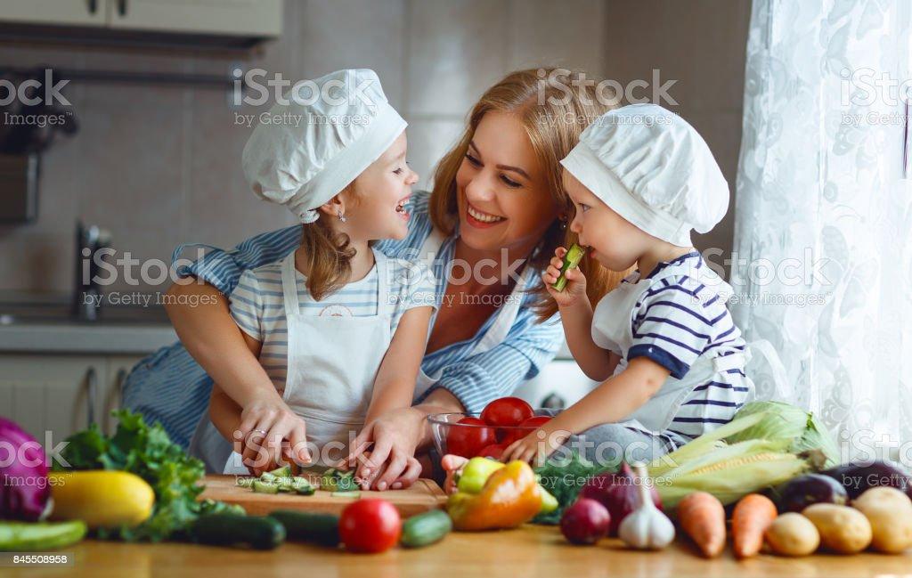Gesunde Ernährung. Glückliche Familie Mutter und Kinder bereitet Gemüsesalat – Foto