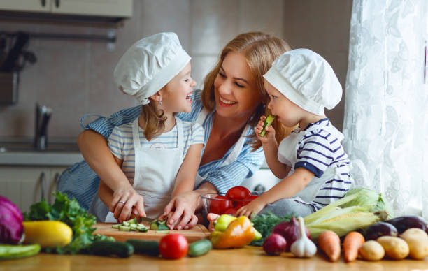 healthy eating. happy family mother and children prepares  vegetable salad - kids cooking stock photos and pictures