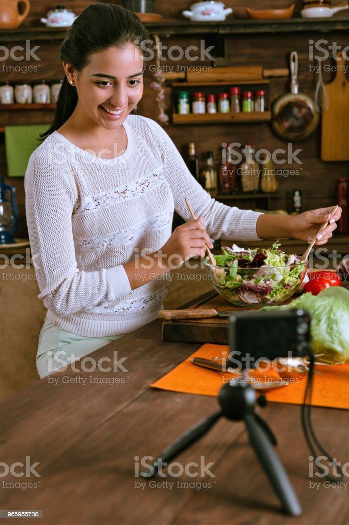 Gezond eten - Hispanic blogger vrouw een vegan salade met organische ingrediënten maken in een rustieke keuken - Royalty-free 20-29 jaar Stockfoto