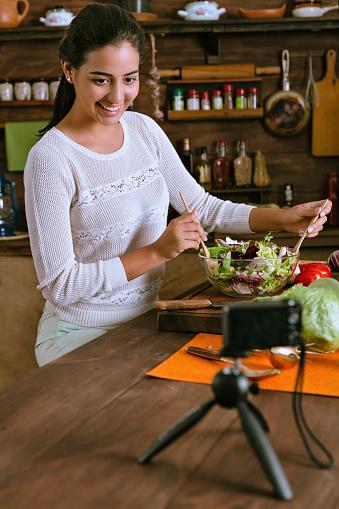 Gezond Eten Hispanic Blogger Vrouw Een Vegan Salade Met Organische Ingrediënten Maken In Een Rustieke Keuken Stockfoto en meer beelden van 20-29 jaar