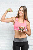 Beautiful woman with bowl full of vegetables. Healthy eating concept.