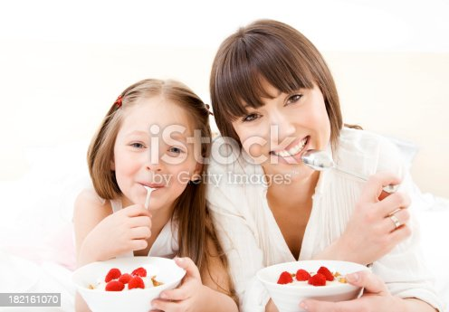 Happy smiling mother and daughter lying on bed and eating healthy food together. Looking at camera.