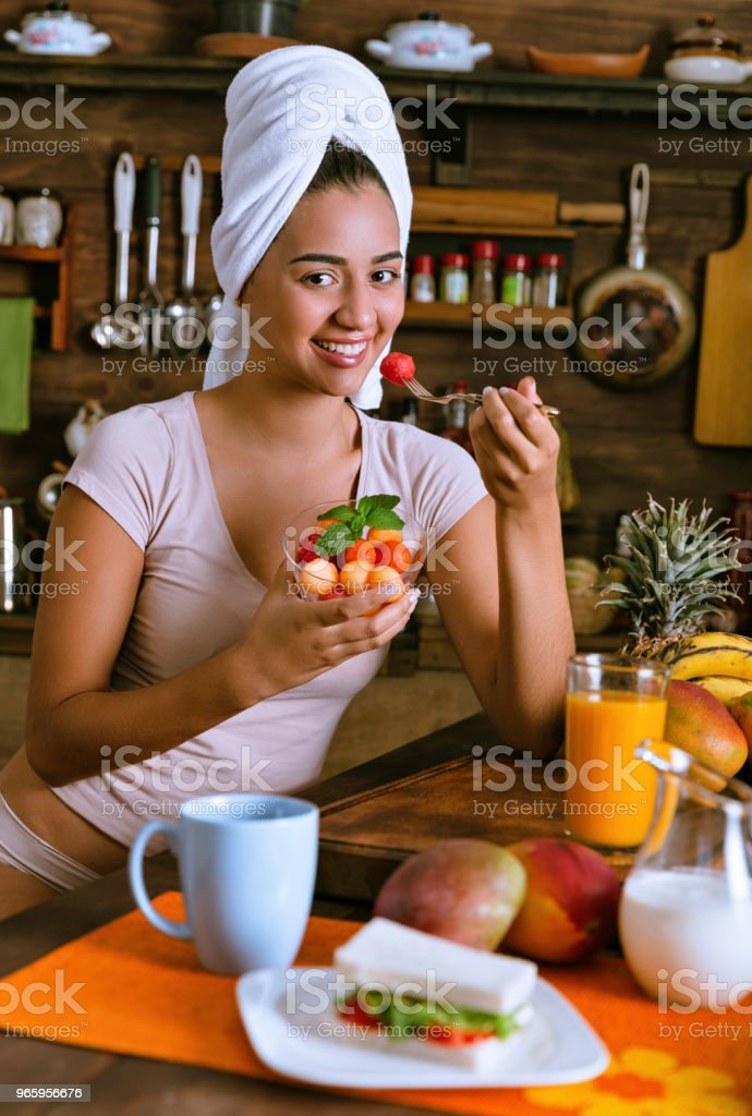 Healthy eating - Relaxed Hispanic young woman in underwear eating fruit salad in the kitchen - Royalty-free 20-29 Years Stock Photo