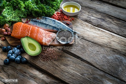 Top view of healthy, antioxidant group of food rich in Omega-3 placed at the top-left corner of a rustic wooden table leaving useful copy space for text and/or logo. The composition includes food rich in antioxidants considered as a super-food like avocado, kale, blueberries, chia seeds, salmon, sardines, olive oil, flax seeds and goji berries. XXXL 42Mp studio photo taken with SONY A7rII and Zeiss Batis 40mm F2.0 CF