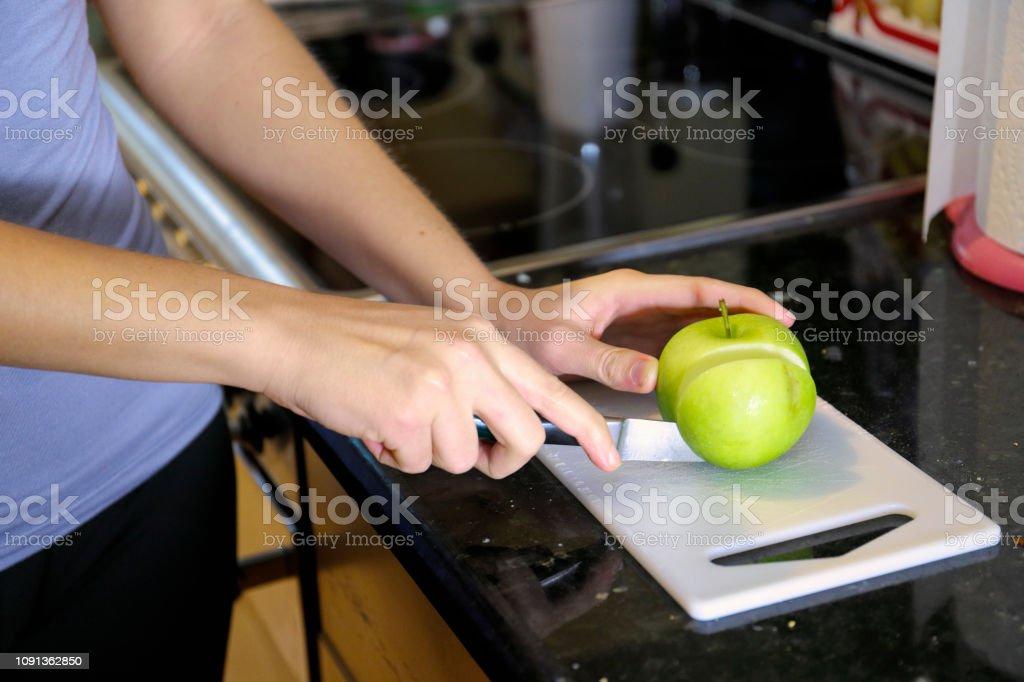 Healthy eating slicing apple beautiful Russian indoor girl stock photo