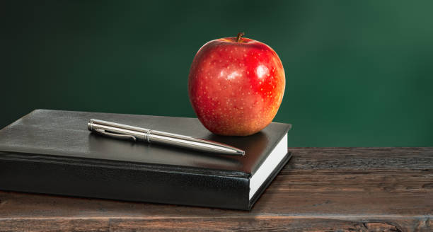 Healthy education concept with apple and book. Still life with red apple, silver pen and black leather notebook or diary on wooden school desk. Green blackboard background. Copy space. teacher appreciation week stock pictures, royalty-free photos & images