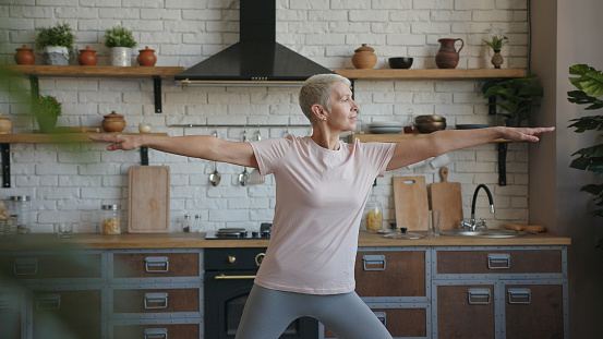 Healthy elderly yoga woman doing yoga exercise at home