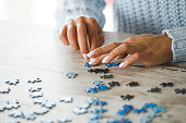 Close up of female hands playing with puzzle pieces on wooden table to spend lockdown time in a healthy entertaining way.
